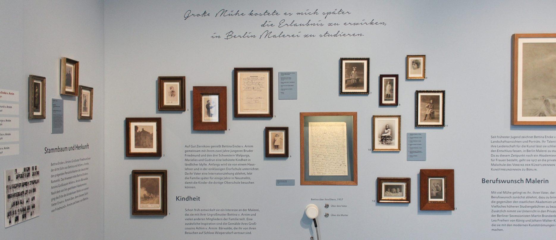 """Wandausschnitt der Ausstellung """"Kunst und Leben – Leben und Kunst"""" mit kleinformatigen gerahmten Schwarz-Weiß-Fotografien und Wandtexten"""