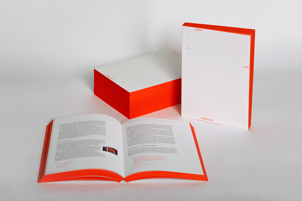 """Das Buch """"Kunst als Negation"""" liegt aufgeschlagen, hochkant stehend und auf einem Stapel"""