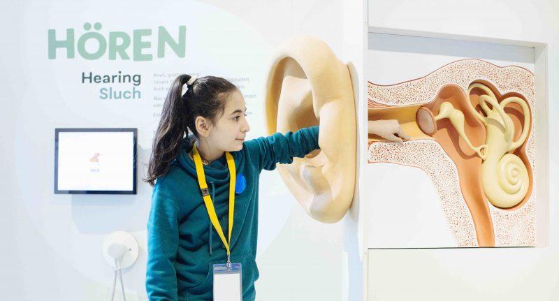 Ein junges Mädchen greift durch ein stark vergrößertes Modell einer Ohrmuschel in den Gehörgang, der dahinter im Querschnitt sichtbar ist.